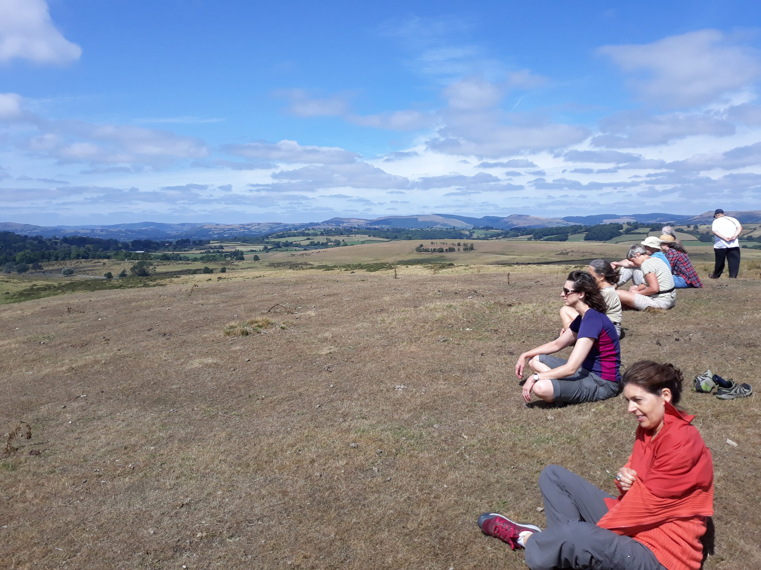 A row of seven people sitting and one standing, looking out over a large field under blue sky and with hills and valleys in the background