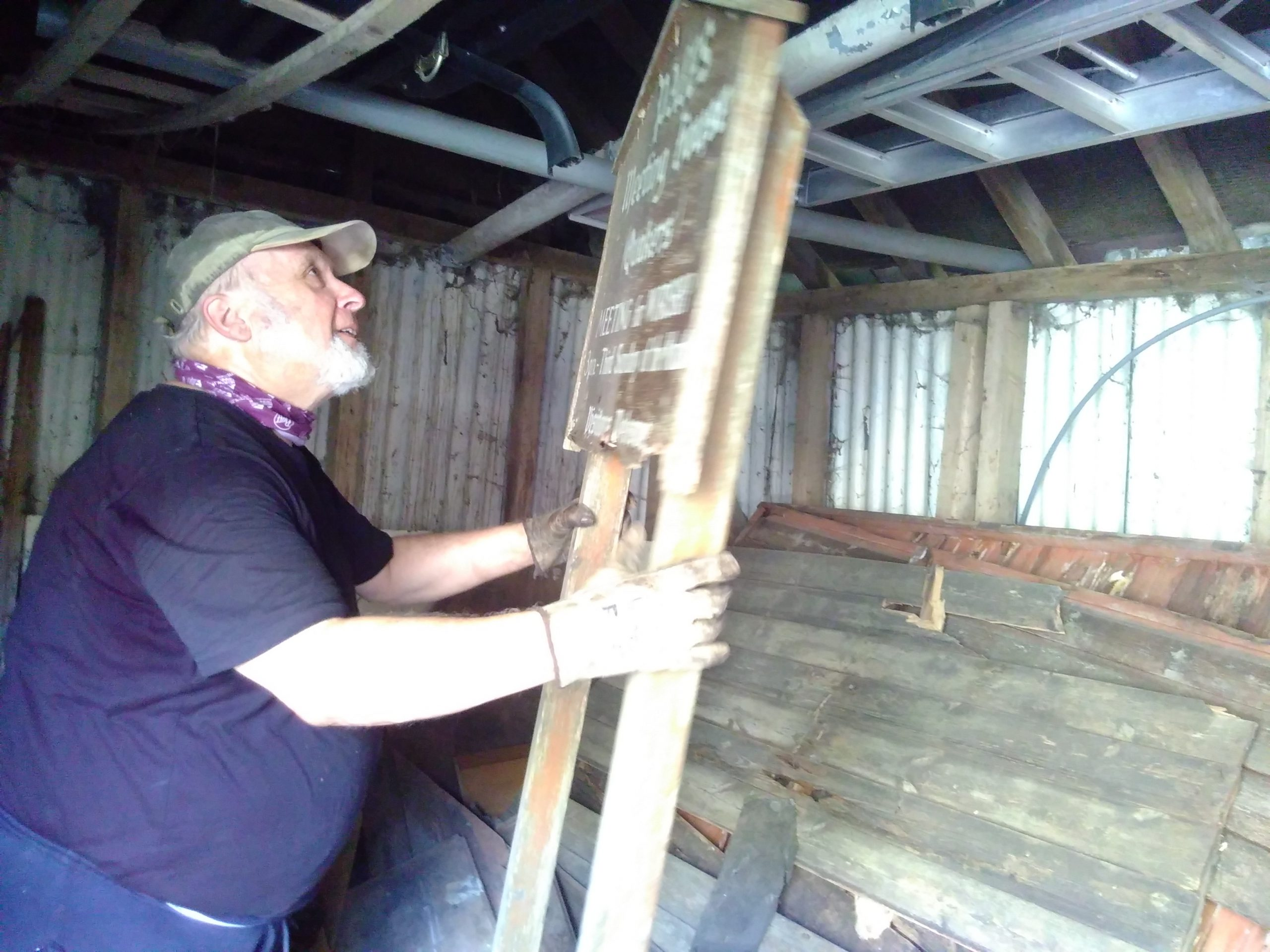 A man is picking up a large sign. The words 'The Pales' are just visible in the sign. It is inside a shed with wood stacked in the background.