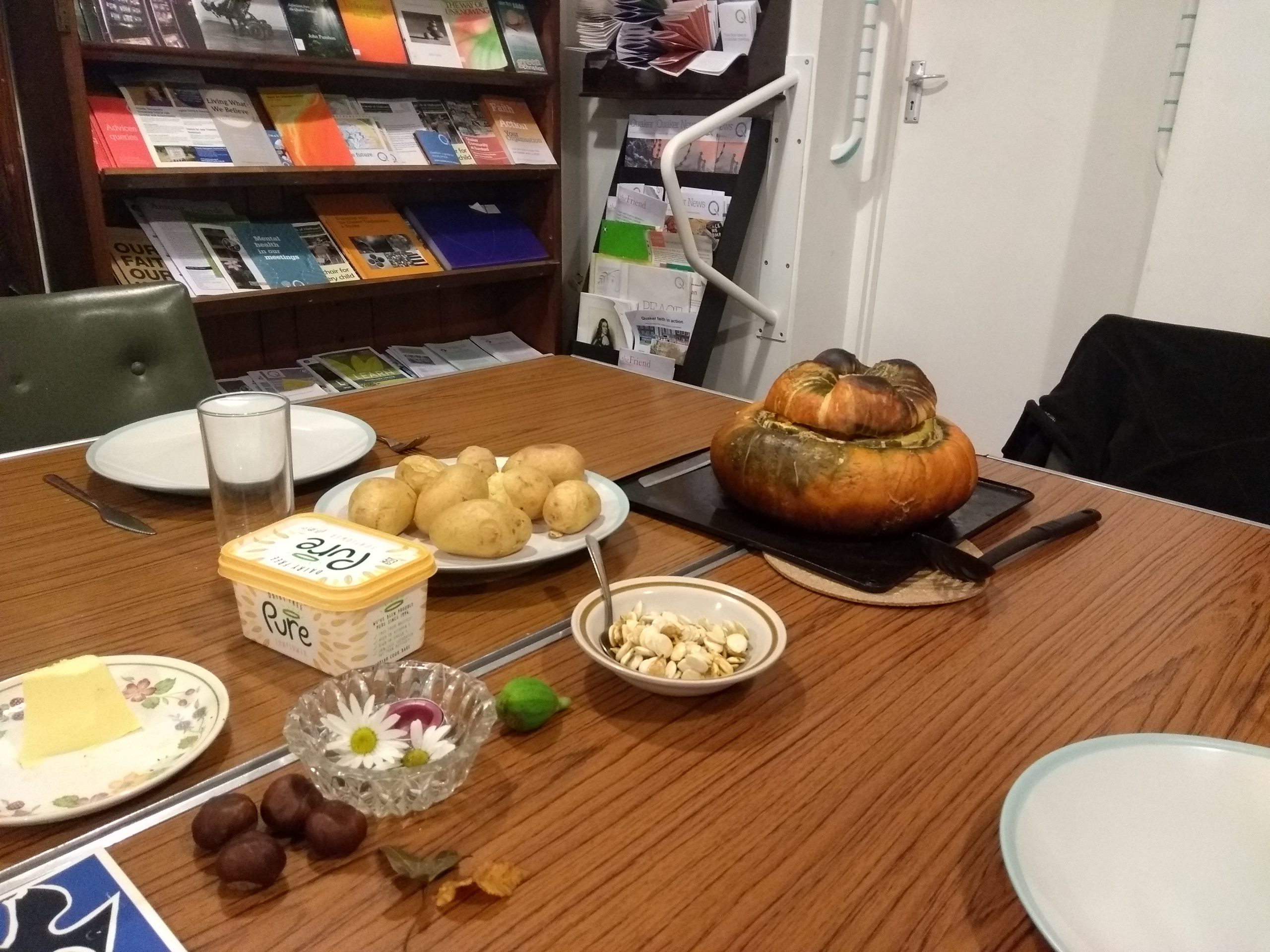 Photo of a dining table, with a large squash, baked potatoes and spread on it, also plates.