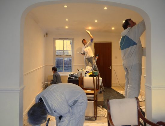Four people with paint brushes in different parts of a room, painting the ceiling and walls