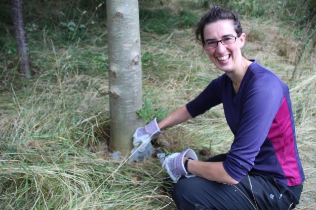 A woman smiles at the camera whilst pulling at a plastic bottle around the base of a tree