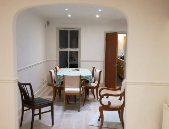 A newly decorated room, looking bright and airy and with a dining table in the middle